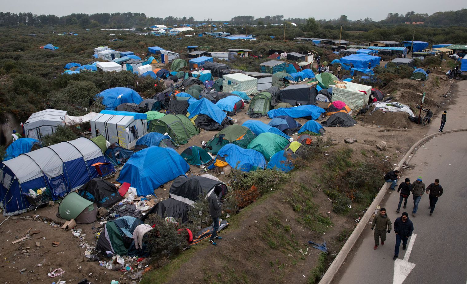 jungle-de-calais-migrants-migrants-walk-past-tents-in-the-new-jungle-make-shift-camp-in-calais_5461950
